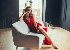 Горячая молодая женщина, одетая в платье длинной алой краски длинном, сексуально показывает ее обнаженные ноги сидя на серой софе стоковое фото