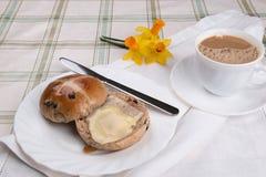 Горячая перекрестная плюшка отрезала и умаслила на белой салфетке чашки чаю плиты Стоковые Фотографии RF