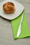 Горячая перекрестная плюшка с зеленой салфеткой и ножом Стоковое фото RF