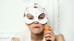 Горячая сексуальная девушка в кожаной маске на белой предпосылке Конец вверх по девушке зайчика пасхи ест морковь изолированную н видеоматериал