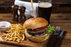 Горячая сервировка бургера на деревянной доске с темным пивом Стоковое Изображение