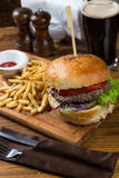 Горячая сервировка бургера на деревянной доске с темным пивом Стоковые Фото
