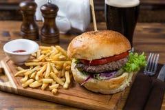 Горячая сервировка бургера на деревянной доске с темным пивом Стоковая Фотография