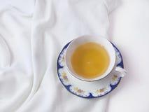 Горячая чашка зеленого чая в белой декоративной чашке фарфора на белой предпосылке Плоское положение Взгляд сверху Стоковое Фото