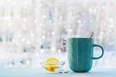 Горячая чашка чаю на нерезкости деревянного стола на фоне окна на зимний день, Стоковое Фото