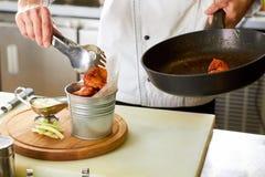 Горячее ведро крыла цыпленка заполняя используя схваты утвари кухни Стоковые Фотографии RF