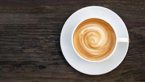 Горячее взгляд сверху пены спирали latte капучино кофе на темной деревянной предпосылке Стоковое Фото