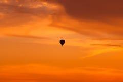 Горячее летание воздушного шара на небе захода солнца Стоковая Фотография