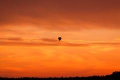 Горячее летание воздушного шара на небе захода солнца Стоковое Изображение RF