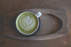Горячее искусство latte зеленого чая на магазине кафа деревянного стола Стоковые Фото