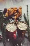 горячее какао с зефирами и круассаном на деревенском деревянном столе с светами рождества Стоковая Фотография