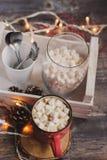 Горячее какао с зефирами на деревянном столе с светами рождества Стоковые Фото