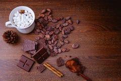 Горячее какао с шоколадными батончиками и напудренным шоколадом на деревянном стоковая фотография rf