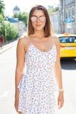 Горячее лето в городе Портрет девушки в светлом белом платье и солнечных очках представляя на горячем после полудня на Стоковые Фотографии RF