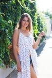 Горячее лето в городе Портрет девушки в светлом белом платье представляя на горячий день на европейской улице Стоковое Изображение RF