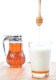 Горячее молоко с медом, опарником меда и ковшом меда на белом backgro Стоковые Изображения