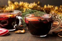 Горячее обдумыванное вино с циннамоном и апельсином в стеклянных чашках и украшения рождества на темной предпосылке Рождество Нов стоковые изображения