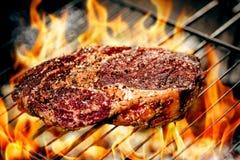 Горячее пряное приготовление на гриле стейка на барбекю лета над горячими гарнированными углями Стоковые Изображения RF