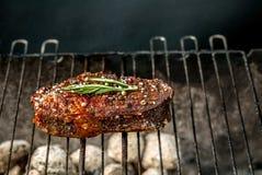 Горячее пряное приготовление на гриле стейка на барбекю лета над горячими гарнированными углями украшенными с ветвью розмариновог Стоковые Изображения