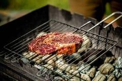 Горячее пряное приготовление на гриле стейка на барбекю лета над горячими гарнированными углями Стоковое Фото