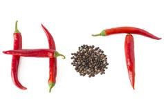 Горячее слово сделанное от накаленного докрасна перца chili и перчинки на белизне Стоковое фото RF