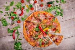Горячее margherita пиццы с мясом, сыром и специями на деревянной предпосылке Много овощи на серой таблице Стоковое фото RF