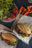 2 горячей сосиски с зажаренными сосиской, томатом и перцем на деревянных животиках Стоковое Фото