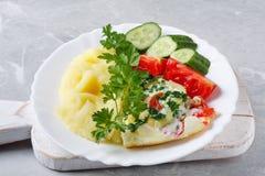 Горячие вкусные картофельные пюре с взбитыми яйцами, томатами, огурцами и свежей петрушкой стоковое изображение