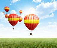 Горячие воздушные шары на зеленой траве Стоковое Изображение