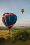 Горячие воздушные шары над зеленым полем риса Стоковые Изображения