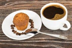 Горячие кофе и булочки в поддоннике на таблице Стоковое фото RF