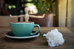 Горячие кофе или capuchino mocha с белыми цветком гвоздики и человеком древесины на деревянном столе Стоковое фото RF