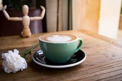 Горячие кофе или capuchino mocha с белыми цветком гвоздики и человеком древесины на деревянном столе Стоковые Изображения RF