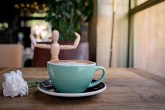 Горячие кофе или capuchino mocha с белыми цветком гвоздики и человеком древесины на деревянном столе Стоковые Фотографии RF