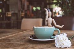 Горячие кофе или capuchino mocha с белыми цветком гвоздики и человеком древесины на деревянном столе Стоковая Фотография RF