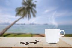 Горячие кофе и кофейное зерно на верхней части деревянного стола на запачканной предпосылке кокосовой пальмы и пляжа Стоковые Фото