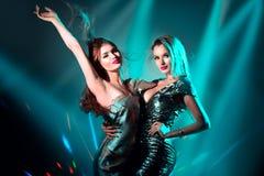 Горячие модельные девушки танцуя в УЛЬТРАФИОЛЕТОВЫХ неоновых светах Партия диско Сексуальные молодые женщины с идеальными тонкими стоковые изображения
