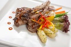 Горячие мясные блюда - нервюры BBQ с зажаренными в духовке овощами и кипеть картошками Стоковые Изображения RF