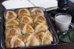Горячие перекрестные плюшки с чашкой кофе, ручки циннамона на таблице стоковая фотография