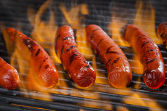Горячие сосиски на пламенеющем горячем гриле барбекю Стоковые Изображения RF