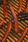 Горячие сосиски на пламенеющем горячем гриле барбекю Стоковое фото RF