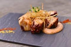 Горячие тапы зажаренного осьминога с соусом на черной плите утеса Стоковое Изображение