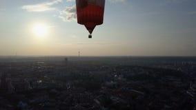 Горячий воздушный шар плавая над городом на зоре, солнце поднимая на горизонт, устремленности сток-видео