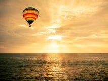Горячий воздушный шар над морем на заходе солнца Стоковое Изображение