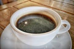 Горячий кофе в белой чашке на таблице стоковые изображения