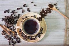 Горячий кофе в деревянной чашке и кофейные зерна разливают на деревянной предпосылке стоковое изображение rf