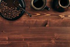 Горячий кофе в черной чашке с фасолями, ложкой и турецким cezve бака с космосом экземпляра на коричневой старой предпосылке дерев Стоковые Фото
