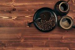 Горячий кофе в черной чашке с фасолями, ложкой и турецким cezve бака с космосом экземпляра на коричневой старой предпосылке дерев Стоковые Изображения