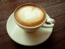 Горячий кофе имеет форму сердца на верхней части с деревянным столом Стоковое фото RF