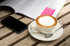 Горячий кофе с мобильным телефоном на таблице Стоковое фото RF